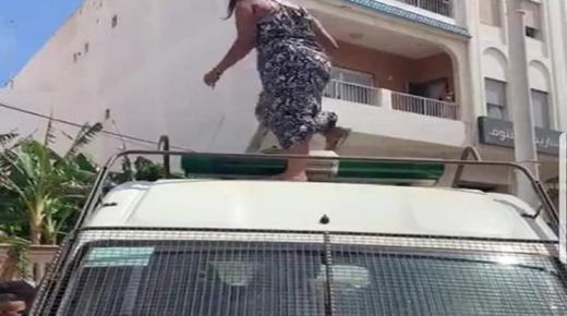 بالفيديو، سيدة تحتج بطريقة غريبة وتصعد فوق سيارة القوات المساعدة
